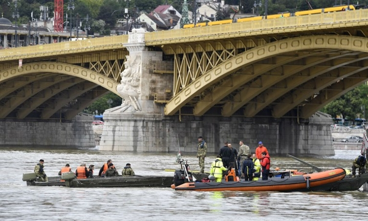 Salvage crews lift the boat which sank in the Danube